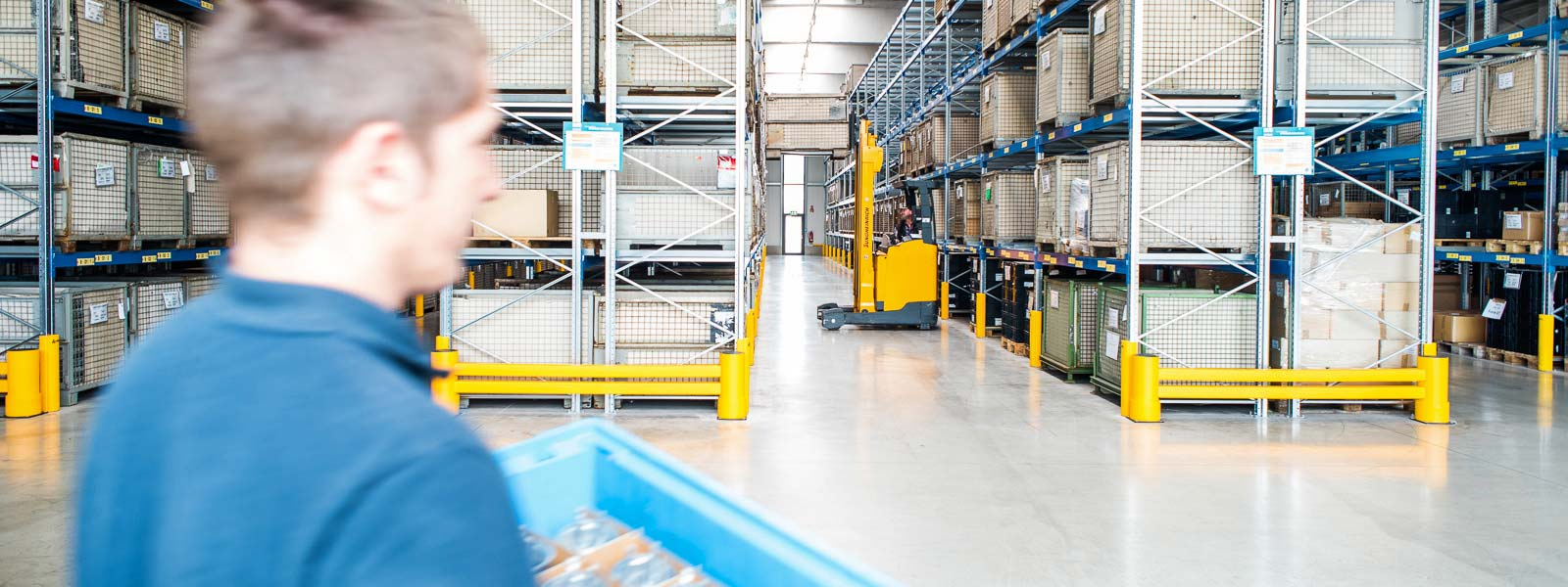 View inside warehouse, employee in front of high-bay racking
